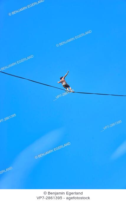 man walking on highline slackline in high heights, Bavarian alps, near mountain Blankenstein, south of Germany