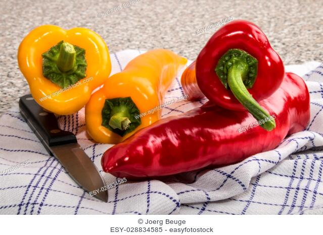 organic red and yellow chili with knife on a kitchen kitchen towel