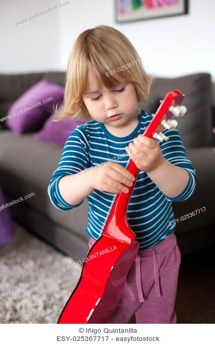 blonde two years old child with striped blue and white sweater playing red spanish little guitar inside home