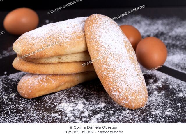 Closeup of leavened savoiardi biscuits sprinkled with icing sugar