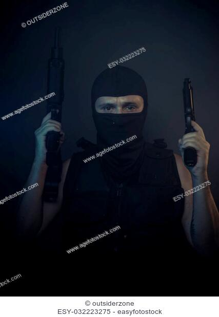 Aggression, terrorist carrying a machine gun and balaclava