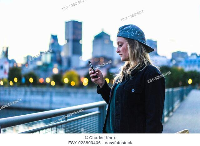 Portrait of young teenage girl texting on her smartphone, Montreal, Quebec, Canada