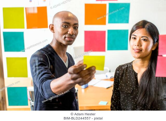 Woman and man reading adhesive notes in office