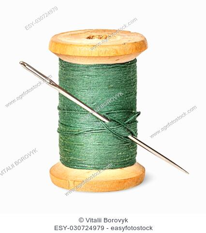 Needle and thread on wooden spool vertically isolated on white background