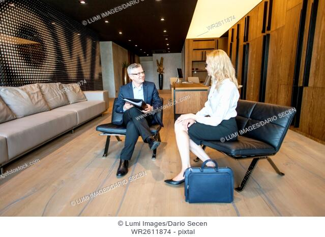 Two business people talking in lobby