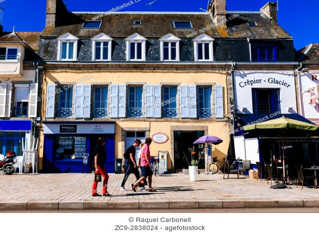 Tourist family passing by a beautiful traditional house on the street, Concarneau, Brittany, France