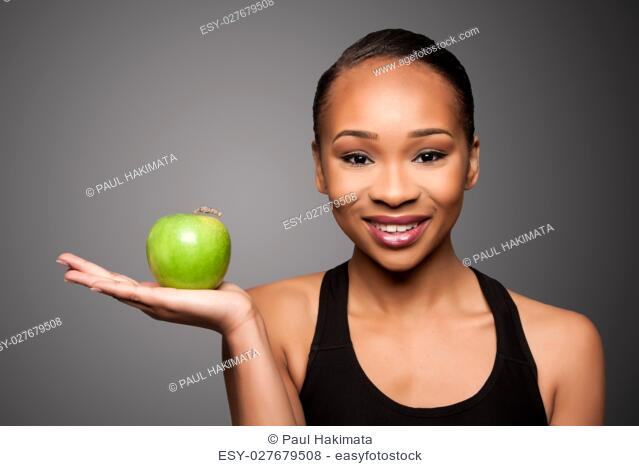 Beautiful healthy happy smiling black asian woman with apple in hand