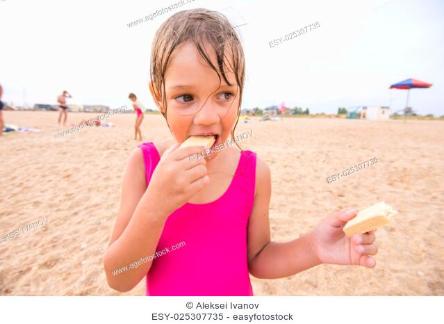 The girl in the pink bathing suit standing on a sandy beach