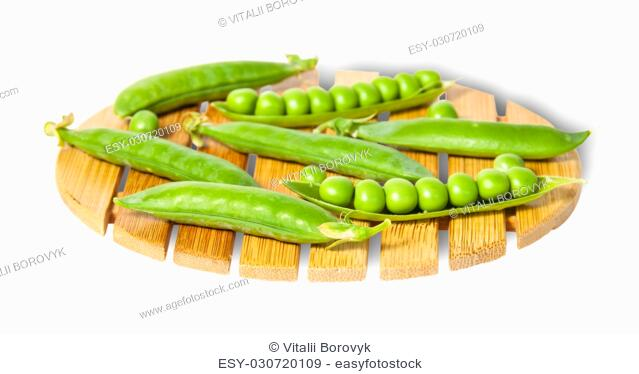 Pods of peas on bamboo small board isolated on white background