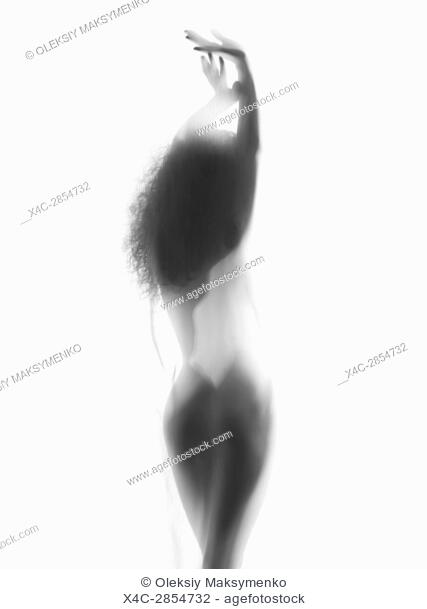 Sexy surreal misty silhouette of a nude woman back standing in bright light behind sheer white curtain