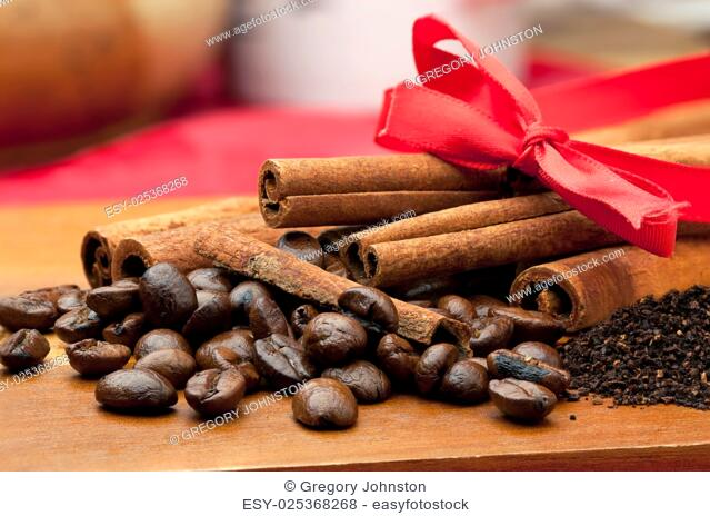 Close up of coffee beans, coffee, grounds, and cinnamon sticks