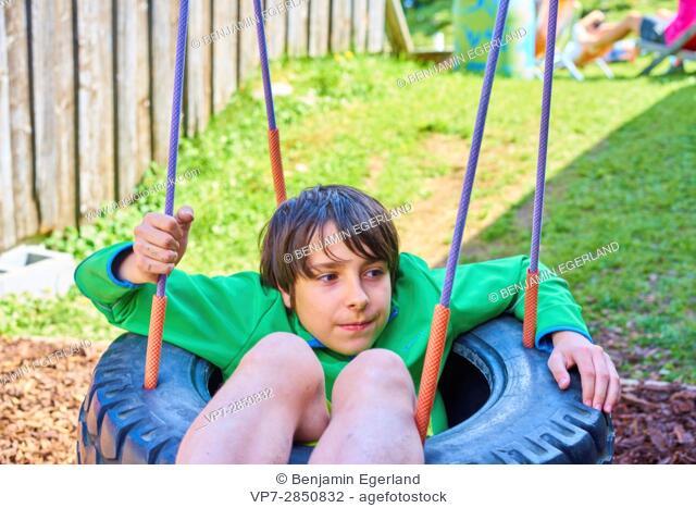 boy sinking in tire swing on playground