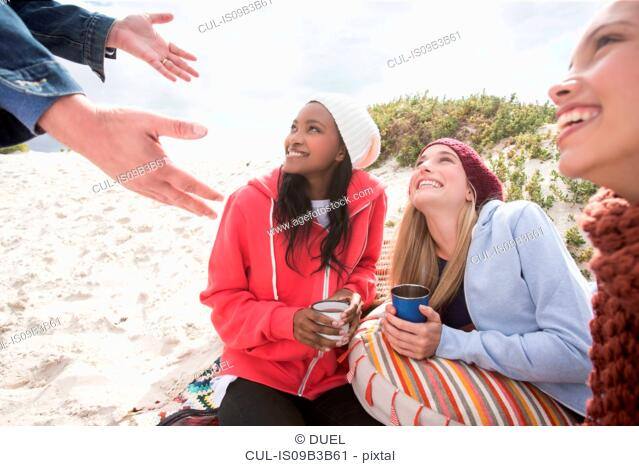 Young women and man picnicking on beach, Western Cape, South Africa