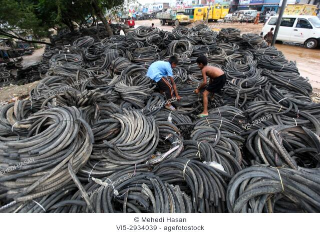 Bangladeshi child laborers handle pieces of old tyres to be recycled in Dhaka. The recycling industry in the Bangladeshi capital plays an important role as it...