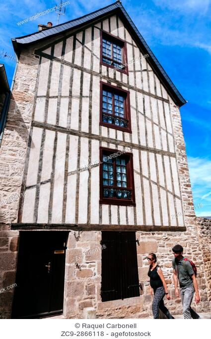 Tourists walking among traditional stone houses. Dinan, Brittany, France