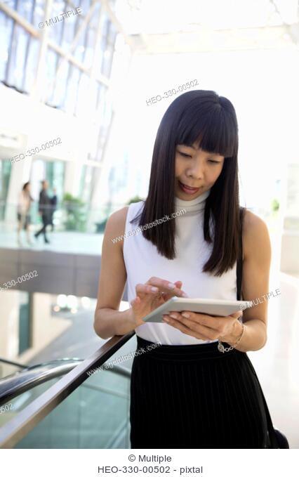 Businesswoman using digital tablet in atrium