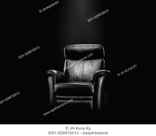 Black leather armchair in spotlight, dark background