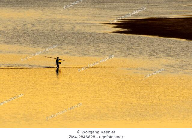 View of the Mekong River with a fisherman silhouetted after sunset near the UNESCO world heritage town of Luang Prabang in Central Laos