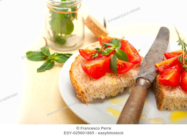 Italian tomato bruschetta with thyme and mint leaves