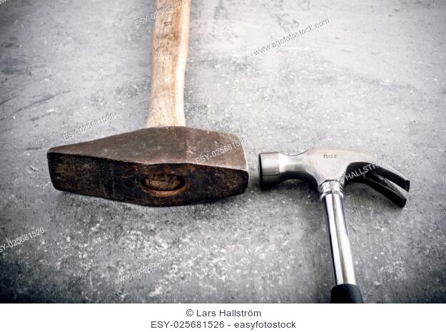 Hammer still life. Two hammers side by side on a stone workbench. Symbol of strength and force. Concept of industrial work tool