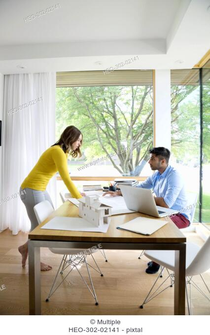 Young couple architects working at dining room table