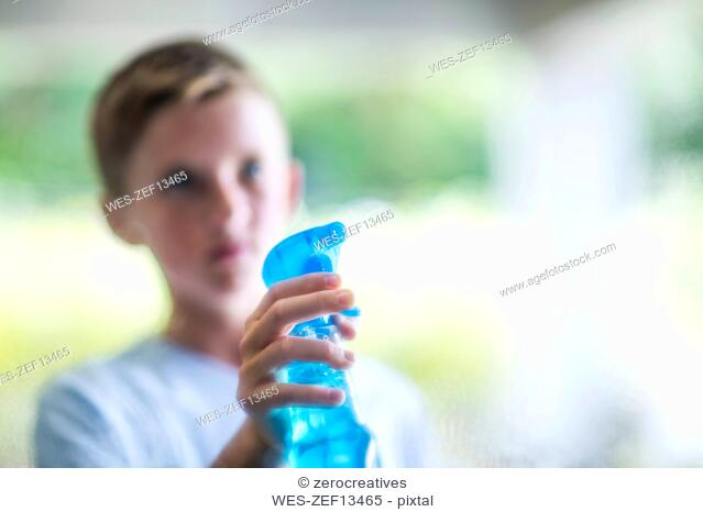 Boy spraying with window cleaner