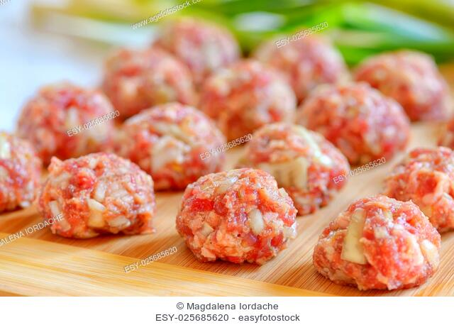 Raw Uncooked Meatballs on wooden plate