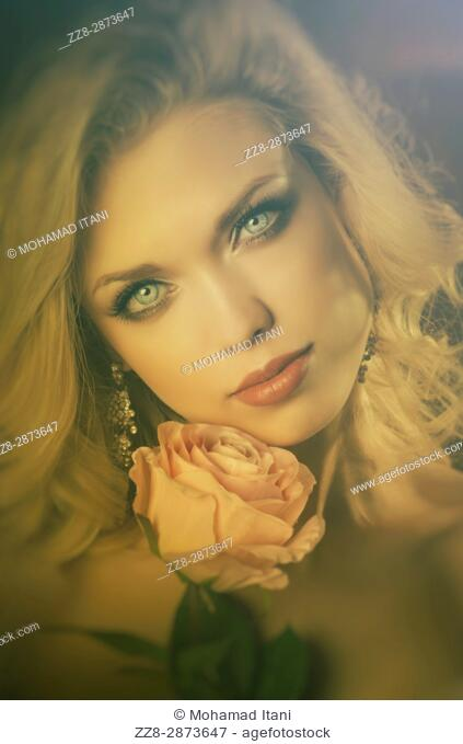 Beautiful young blond woman holding a pink rose