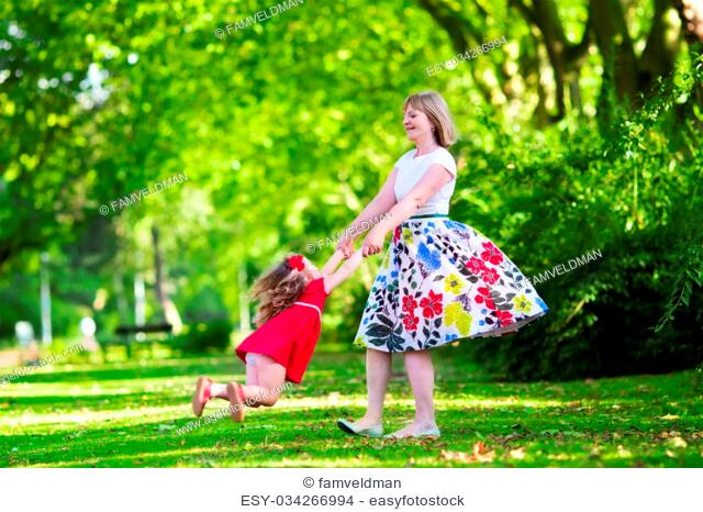 Family with kids playing in a park. Woman and little girl spin and dance in the garden. Grandmother and granddaughter play outdoors