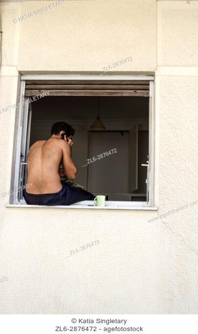 Caucasian shirtless man sitting on a window and talking own his cellular phone