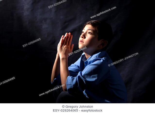 A young boy folds his hands and raises his head in prayer to God