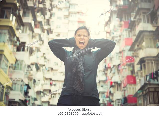 Stressed girl screaming in front of apartments, Yick Cheong Buildings in Quarry Bay, Hong Kong. China