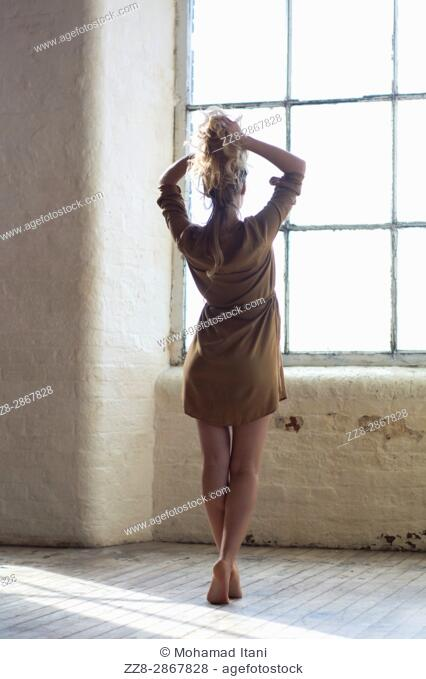 Rear view of a blond woman hands on hair looking out of the window