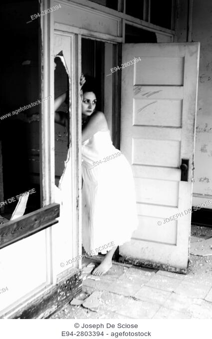 A 25 year old woman wearing a white dress leaning on a doorway in an abandoned office building