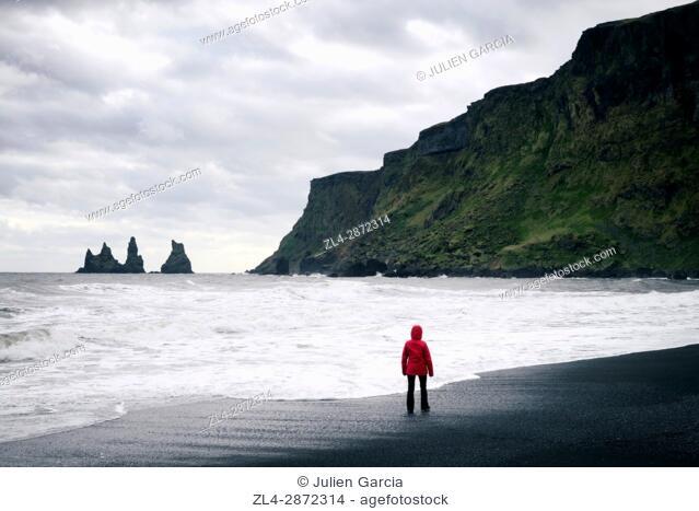 Iceland, Sudurland region, Vik i Myrdal, Vik beach, woman on the black sand beach and Reynisdrangur sea stacks, Model Released