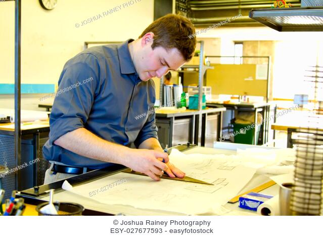 An architect studies in his college work building while drawing plans and preparing work for a class