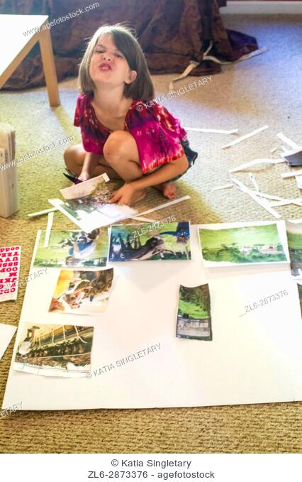 Young caucasian girl doing a project for school, she is cutting, gluing and thinking about the outcome of the project