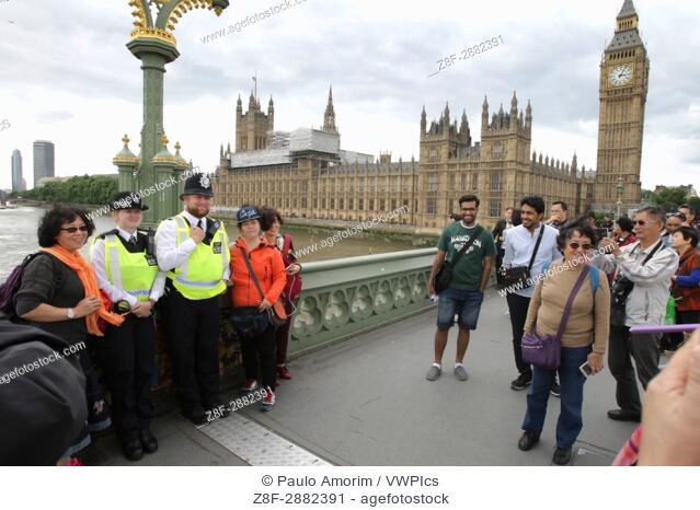 Scene London after the terror attack - Tourists pose for the picture with police officers at Westmisnter bridge on June 4, 2017 in London, England