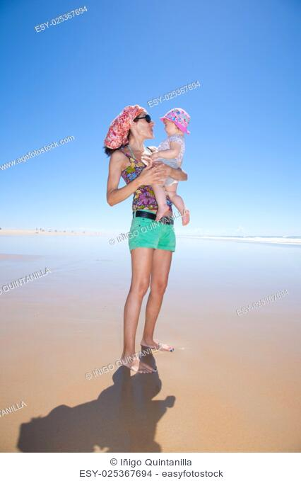 happy woman with sunglasses green shorts headscarf and baby pink hat in arms at beach Conil Cadiz Spain