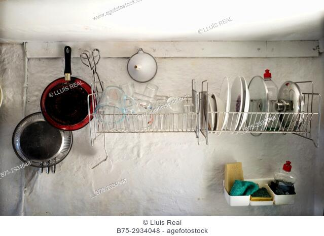 Old and simple kitchen in a fishing lodge with cooking utensils, gas cooker, pots, dishes, etc. Sa Mesquida, Mahó, Minorca, Balearic Islands
