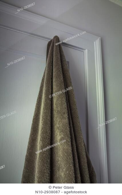 Bath towel hanging on hook on closed bathroom door