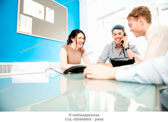 Colleagues in meeting, man on telephone