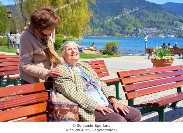 senior woman caring about happy old friend