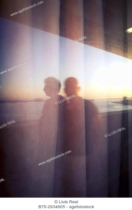 Silhouette of two unrecognizable men on the deck of a ferry boat in port. Mediterranean Coast, Palma, Majorca, Balearic Islands