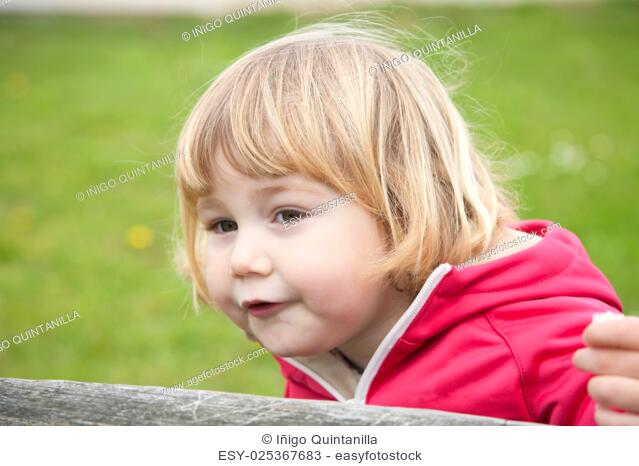 little blonde cute child sitting looking at and eating bread piece with green grass background