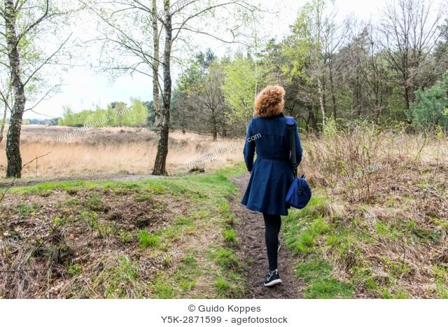 Regte Heide, Riel, Netherlands. Red headed caucasian woman strolling a nature reserve park and forrest on a free weekend afternoon
