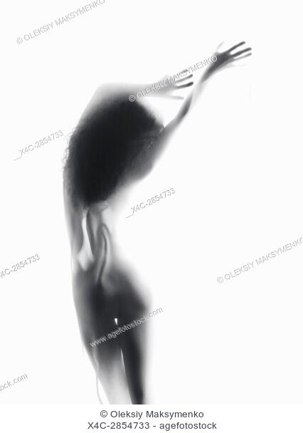 Beautiful graceful silhouette of a naked woman nude back standing in glowing misty bright light behind a white sheer curtain