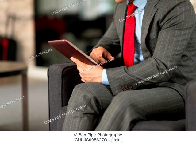 Neck down view of businessman sitting in office using digital tablet