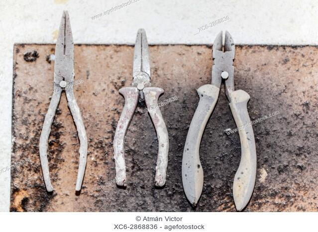 panel of pincers or pliers hanging on a white wall