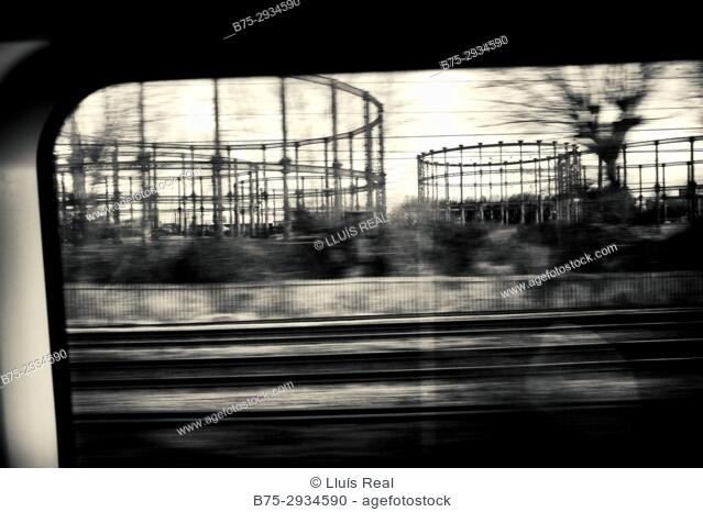 Metallic structures of gas towers seen from a moving train. Newham, East London, England